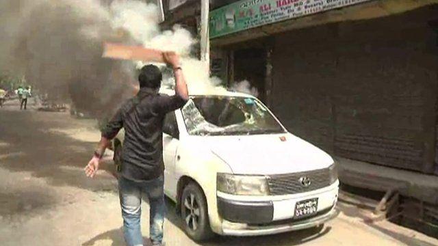 Protester striking car with baton