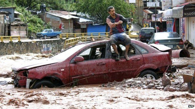 Man on top of car in flooded Mexico