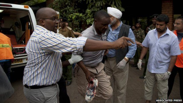 An injured person is helped on his arrival at the Aga Khan Hospital in Nairobi after an attack at the Westgate Mall