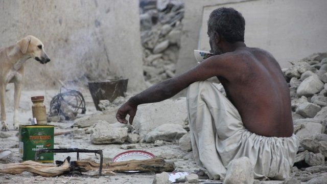 A survivor of an earthquake sits as he takes tea on the rubble of a mud house after it collapsed following the quake in the town of Awaran