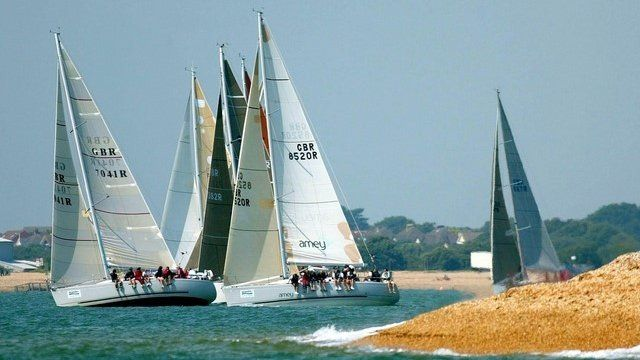 The class three yachts tack away from the beach in the eastern Solent off Alverstoke