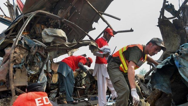 Pakistani volunteers search a destroyed bus