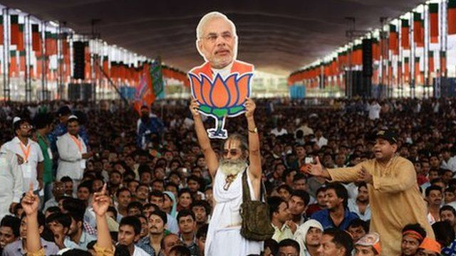 A supporter of the Bharatiya Janata Party holds an image of Narendra Modi.