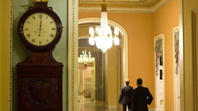 A clock outside the Senate chamber shows one minute past midnight
