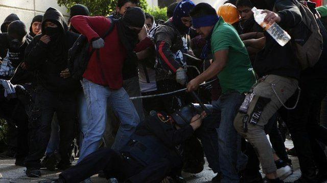 Demonstrators hit a police officer in Mexico City during protests commemorating the 1968 Tlatelolco massacre