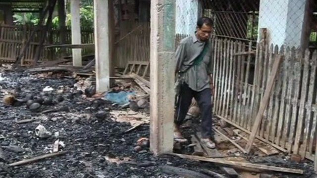 Burma villager walks through torched building
