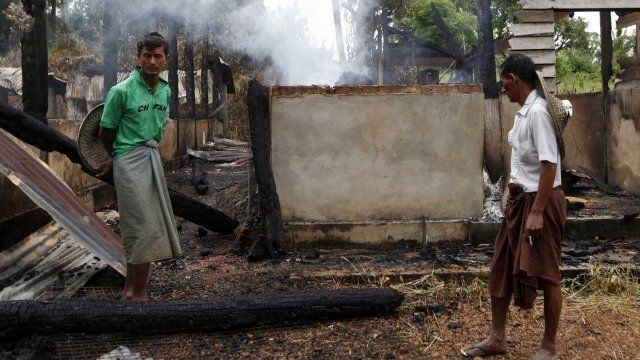 Muslims stand by a burnt mosque as smoke rises from debris in Thabyuchaing village, Thandwe township, Rakhine State