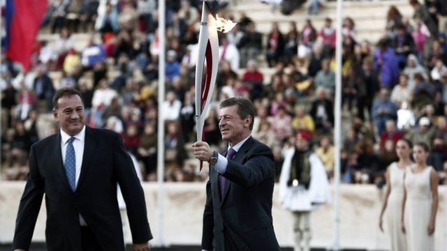 "Russia""s Deputy Prime Minister Kozak raises an Olympic torch for the Sochi 2014 Winter Games next to President of the Greek Olympic Committee Kapralos"