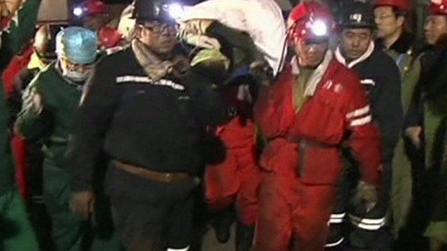 Miner rescued in China being taken by rescue team to an ambulance