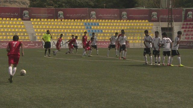 Footballers on pitch in Afghanistan