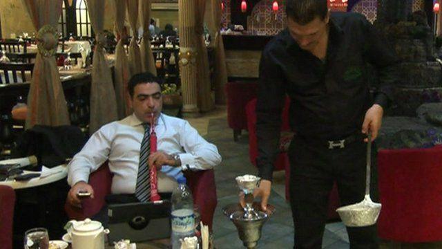 Man using laptop and smoking hookah pipe