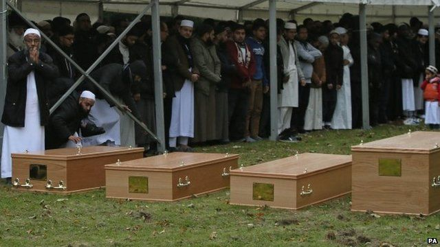 Mourners and four coffins