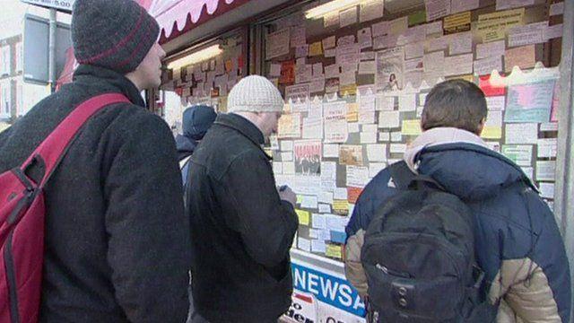Men looking at job adverts in shop window