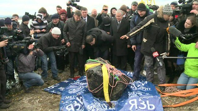 People crowd around a part of what is thought to be the Chelyabinsk meteor in Russia