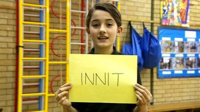 Girl holding sign reading 'innit'