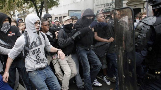 Highschool students face riot police officers as they demonstrate against the police expulsions of immigrant families, including some of their classmates