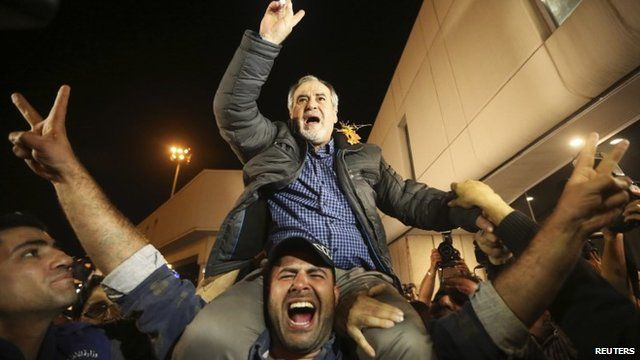 One of the newly released hostages is carried on the shoulders of his son