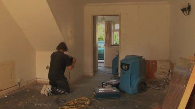 Builders repairing flooded house