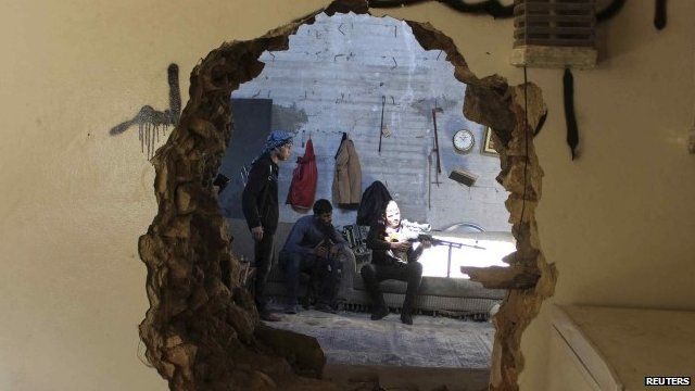 FSA fighters seen through hole in wall in Aleppo