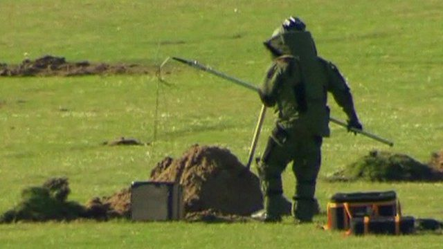 Member of bomb squad lowering box into hole