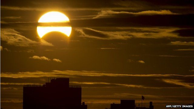 A partial Solar eclipse is seen just after sunrise over the Queens borough of New York across the East River on November 3, 2013
