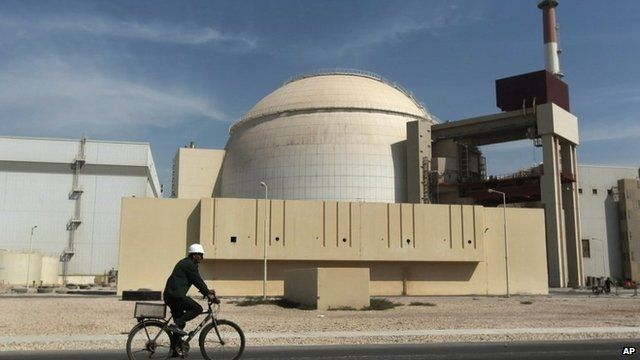 A man rides a bicycle in front of the reactor building of the Bushehr nuclear power plant, Iran