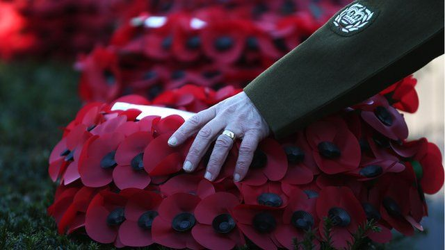 Solider places his hand on wreath