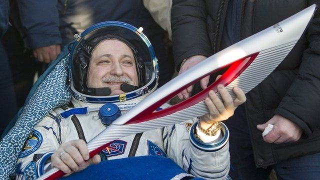 Television images showed the Sochi Olympic torch and the crew of the Soyuz rocket landing back on Earth