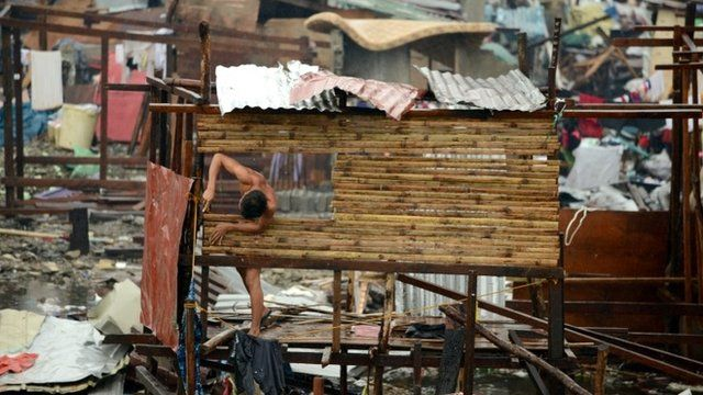 A man reconstructs his destroyed house in Tacloban, eastern island of Leyte