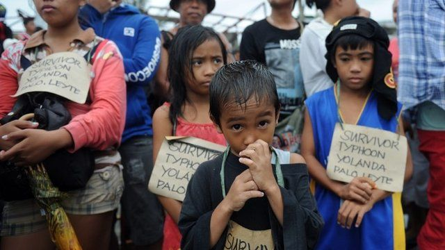 Survivors of the super Typhoon Haiyan, wait for a C-130 military plane at Tacloban airport, Leyte province, central Philippines