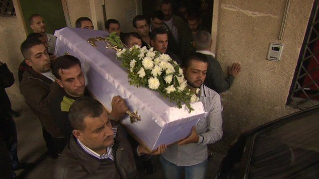 Family members bring out the coffin of a child who was killed after a mortar attack in Damascus