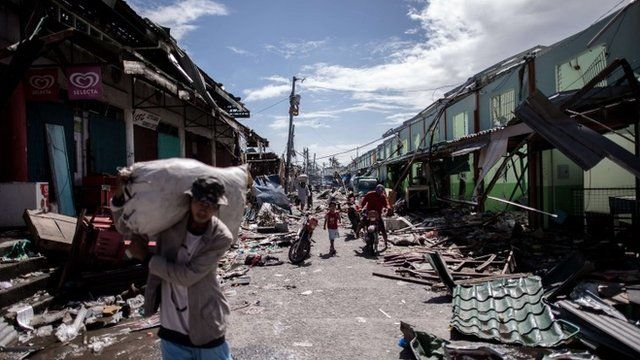 People make their way past shops destroyed by Typhoon Haiyan in Tanauan, on the eastern island of Leyte