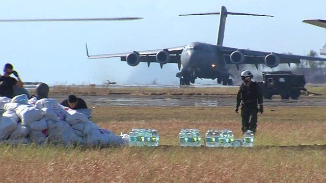 Landing plane, sacks of food, bottles of water