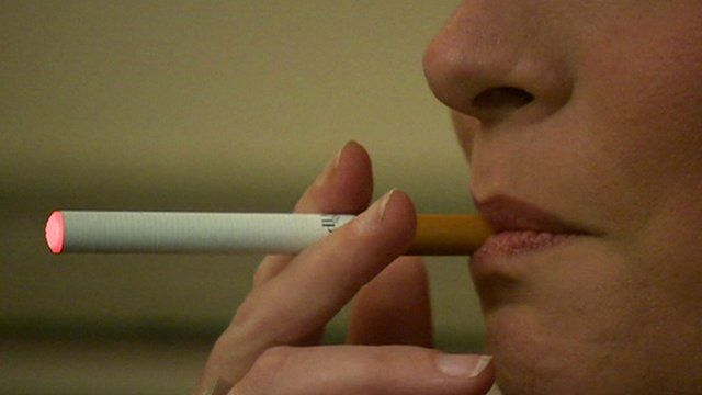 Woman inhales on e-cigarette