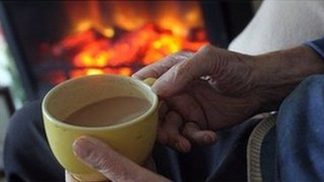 pensioner has cup of tea by the fire