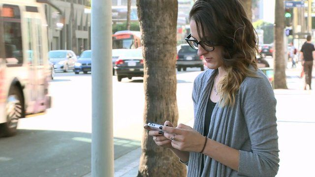 Woman uses phone in street