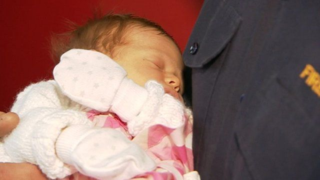 Baby Grace held by firefighter
