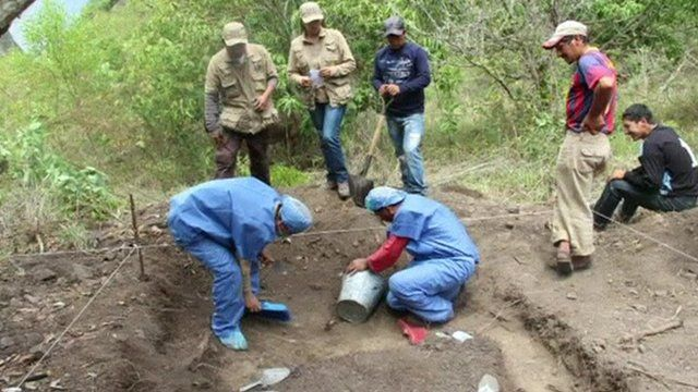 Forensic teams works on a mass graves