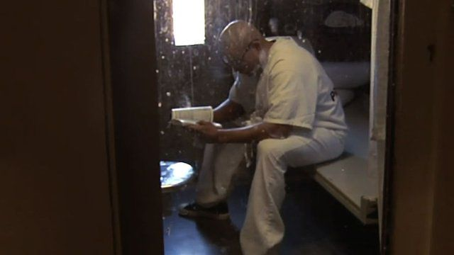 Man reads a book in solitary confinement cell