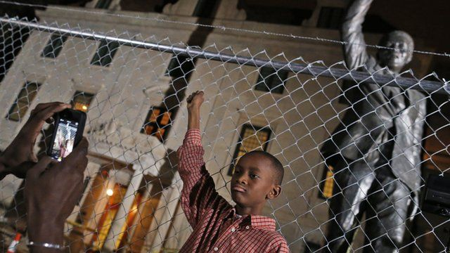 Young boy poses in front of Nelson Mandela statue