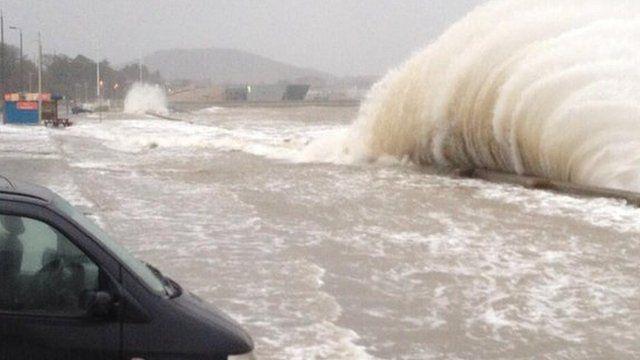 Waves crash over the sea wall at Porth Eirias, Colwyn Bay