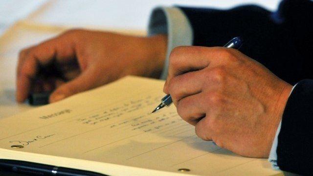 David Cameron signing the book of condolence