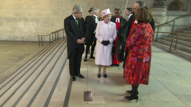 The Queen stands near a plaque dedicated to Nelson Mandela