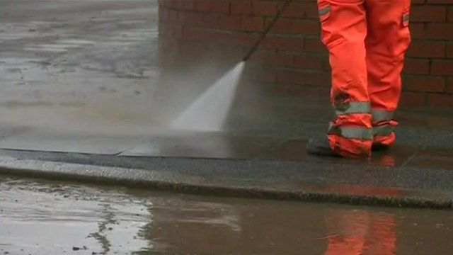 Workman cleans the road after the flooding