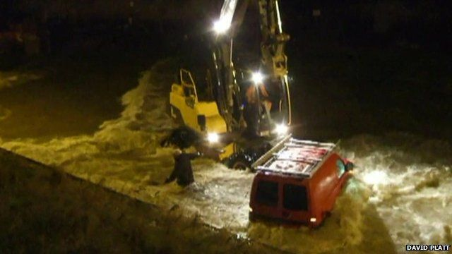 A man and a fork lift truck avoid being swept into the water while trying to recover a van
