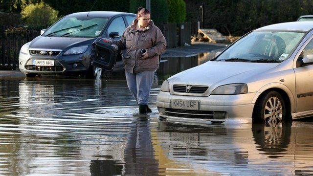 Woman carries baby seat retrieved from car on a flooded street