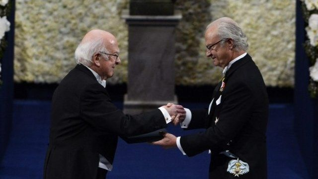 Peter Higgs receives his Nobel Prize in Physics from Sweden's King Carl Gustaf