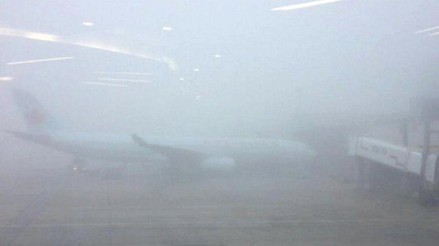 Plane barely visible through fog, London