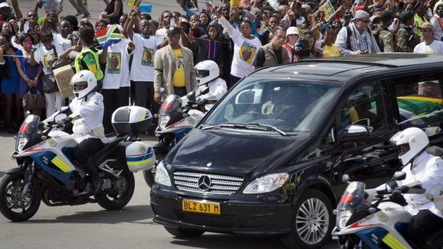 Crowds surround the hearse carrying Nelson Mandela's body