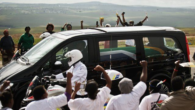 People cheer as the hearse carrying Nelson Mandela's coffin passes by on the way to Qunu